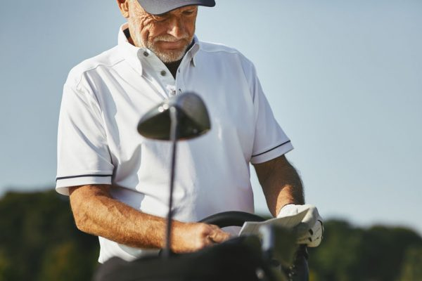 Sporty senior man reading his scorecard while enjoying a round of golf on a sunny day